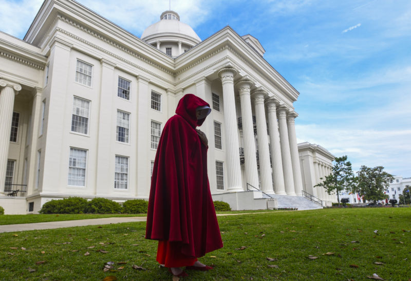 A woman in a red hooded cloak stands in front of a Neo-Federalist building.