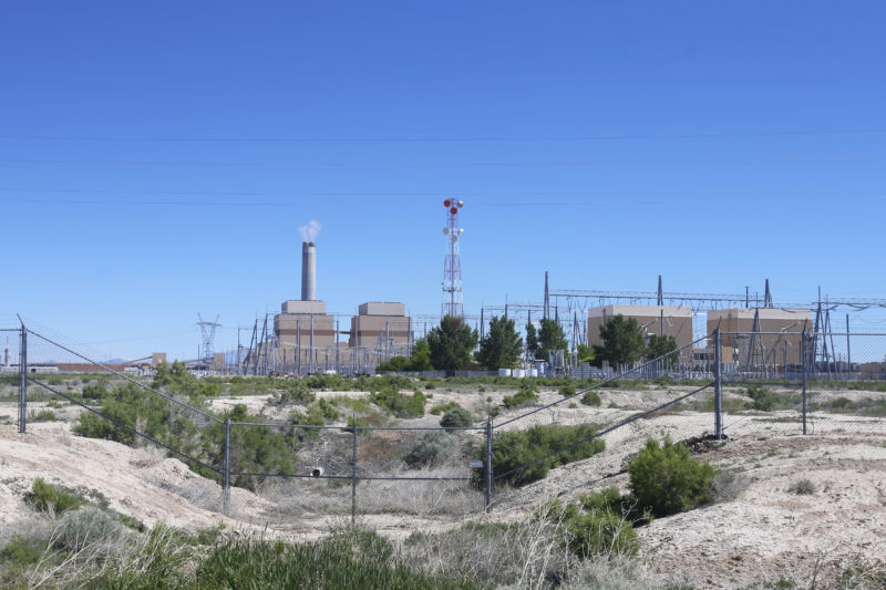 Coal-fired power plant beyond a fence.